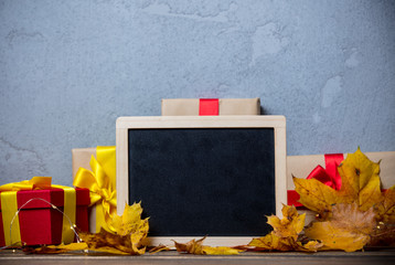 Little gifts with blackboard and leaves on background.