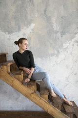 Woman sitting on wooden stairs while looking away