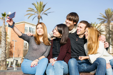 Group of teen friends taking a selfie with their phone outside.