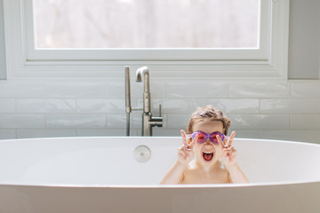 Cute young girl with swim goggles making the victory sign in a bathtub