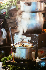 Pot in gas stove in a food stall with steam coming out