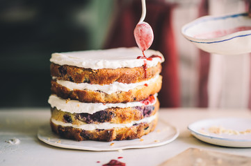 Woman decorating delicious home made cake indoors, in the kitchen