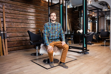 Confident Male Hairdresser Sitting On Chair At Beauty Salon