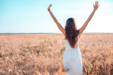 A girl in summer wheat field, raises her hands white dress, tanned skin, happy on vacation in the fresh air. A sunny day. Enjoying nature. Freedom of choice.