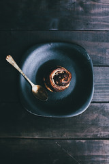 chocolate bun on a plate with a golden spoon