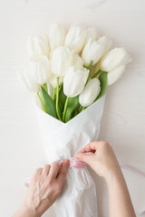 Woman arranging white tulips bouquet