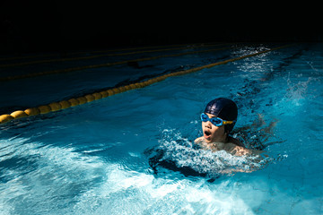 A young swimmer nearing the finish in a breast stroke event for a swimming competition.