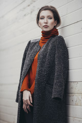 Beautiful woman in a grey coat against a white wall