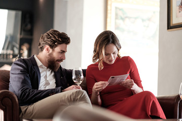 Elegantly Dressed Man and Woman Sitting at the Restaurant