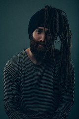 Man with dreadlocks sticking out of a wool hat.