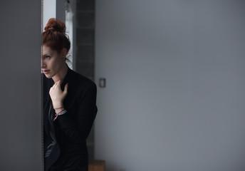 Young caucasian woman sitting near window on rainy day - thoughtful