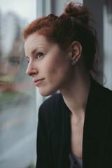 Young, thoughtful caucasian woman sitting near window on rainy day
