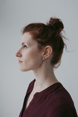 Serious profile portrait of red head woman on simple white background