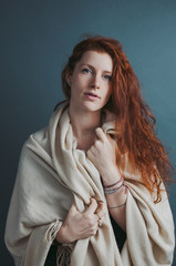Portrait of young red head woman with blanket on solid background