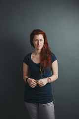 Serious portrait of young red head on solid background