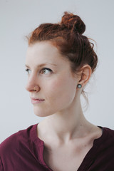 Serious portrait of red head woman on simple white background