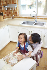 little asian girl having fun with her mother in the kitchen