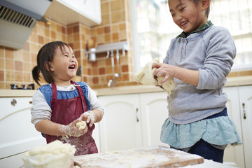two little asian girls having fun in the kitchen