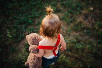 Small toddler child walking around with a teddy bear in red suspenders.