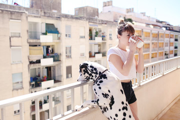 Girl drinking coffee with a dalmatian dog
