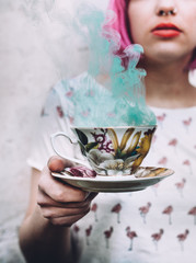 girl holds  a teacup with blue smoke