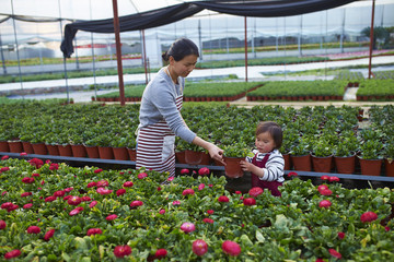 little asian girl working in the flower nursery with her mother