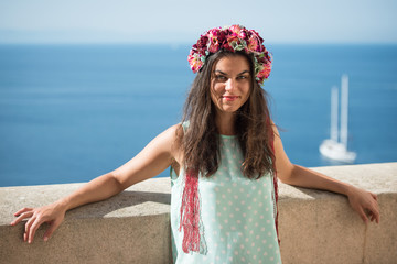 Young woman in blue shirt with flower head band, beautiful sea view in background