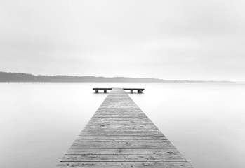landing stage on lake in black and white