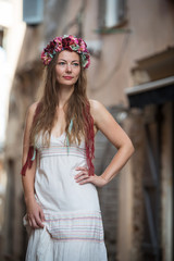Detail of young woman in white dress with flower head band in streets of Bonifacio, France
