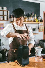 Young coffee shop owner making coffee