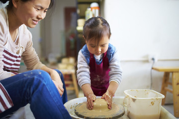 asian woman working in the pottery with her daughter