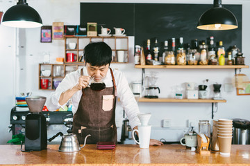 Young coffee shop owner tasting just made coffee