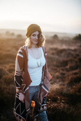 a woman standing in the heath in sunset light