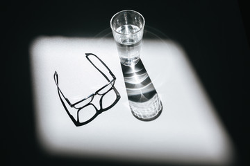 Close up photo of glasses and glass of water on office table. Glasses and glass of clear water on table with beautiful shadows