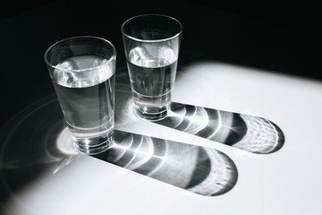 Close up photo of two glasses of water on office table. Amazing photo of glasses with clear water standing on table with shadows