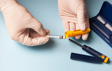 A man in medical gloves holds a syringe for subcutaneous injection of hormonal drugs in the IVF protocol in vitro fertilization Pregnancy, help to his wife.
