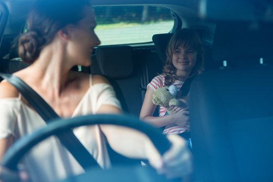 Woman driving a car while daughter sitting in the backseat of