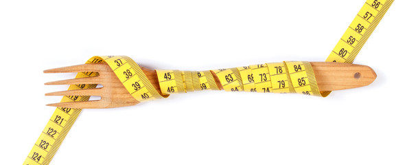 Wooden fork wrapped in centimeter on white background, concept of lose weight and healthy lifestyle