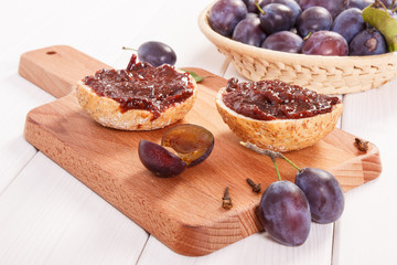 Fresh prepared sandwiches with plum jam on wooden cutting board, breakfast concept