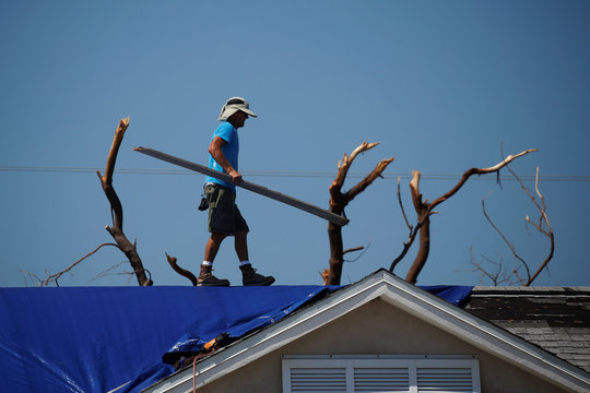 A roofer works on attaching a blue tarp to a roof following Hurricane Irma in Ramrod Key, Florida