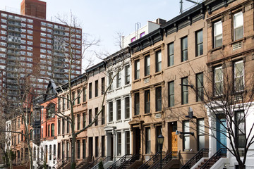 Row of colorful historic brownstone buildings along a block in Manhattan, New York City