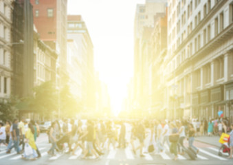 Crowds of people crossing a busy street in New York City with the light of the bright light of the sun glowing in the blurred background
