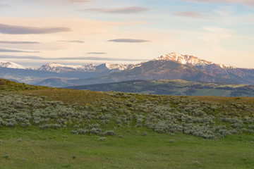 Blacktail Plateau photographed at sunrise. Rugged, snow capped mountains are in the distance with foothills, grass and sagebrush in the foreground.
