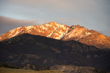 Electric Peak with patches of snow lit by the setting sun and photographed from Yellowstone National Park.