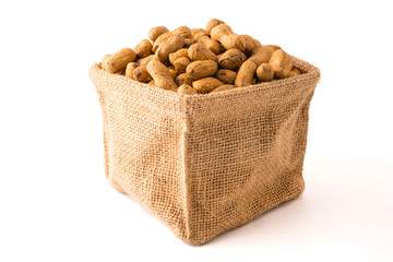 Peanuts in burlap bag on white background.