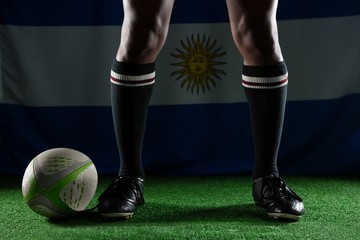 Low section of rugby player standing against Argentinian Flag