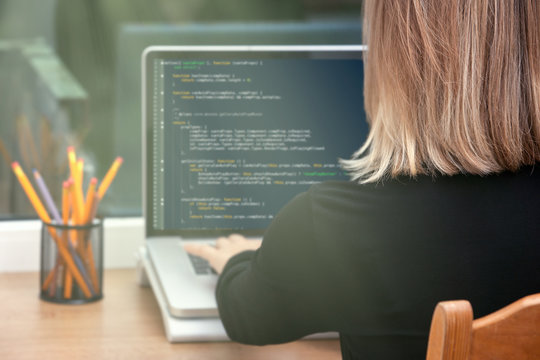 woman freelance programmer working from home. website code on screen.