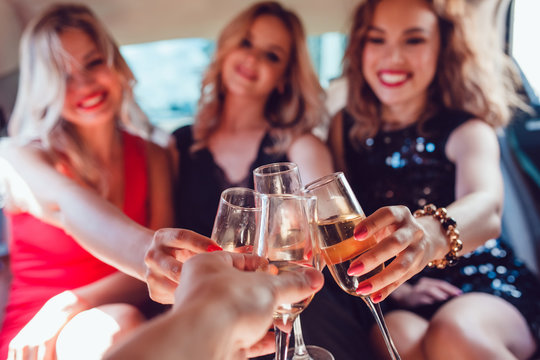 Pretty women having party in a limousine car and drinking champagne.