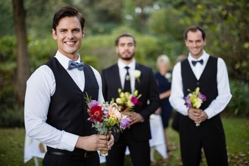 Bridegroom and best man standing with bouquet of flowers in