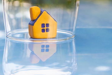 The concept of insurance and protection of housing. Miniature yellow toy house under a glass dome with reflection on the surface. Selective focus